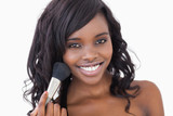 Woman smiling while holding a makeup brush