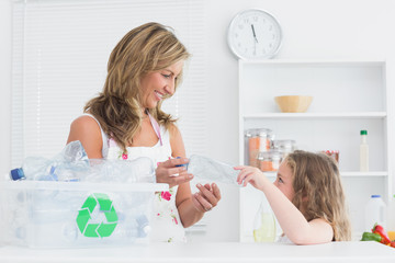 Mother sorting waste with her daughter
