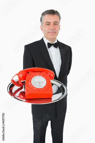 Well-dressed waiter holding a phone on a silver tray