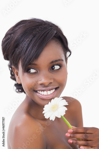Woman looking away while smiling and holding a flower