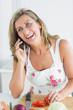 Woman calling during preparing vegetables