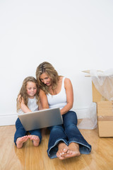 Daughter and mother looking at laptop