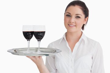 Woman holding tray with glasses of red wine