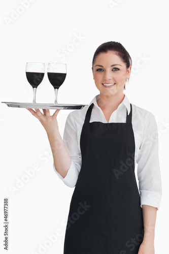 Pretty waitress holding two glasses of wine