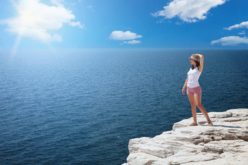 Young woman standing on cliff's edge and looking to a sea