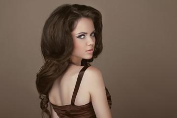 Elegant Woman with beauty long brown hair posing at studio