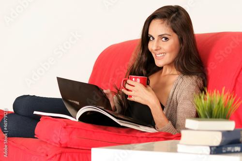 Schöne Frau liegt gemütlich auf der Couch