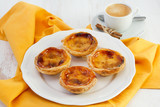 Portuguese pastries on the plate with a cup of coffee