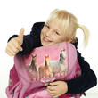 Cute blond girl child with school bag shows thumb up
