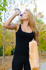 Woman athlete drinking bottled water