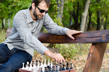 Man playing chess on a wooden bench