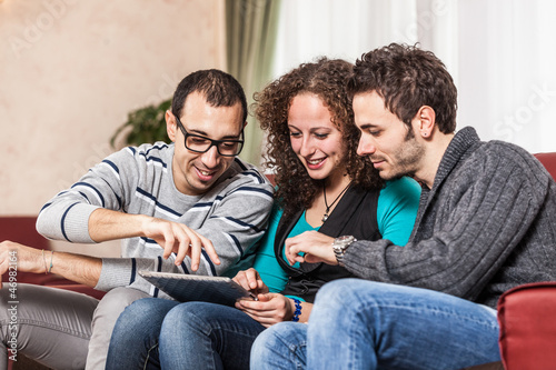 Three Friends with Tablet PC on a Sofa