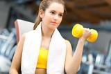 Woman lifting dumbbells - 46982305