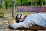 Man sleeping on a wooden bench