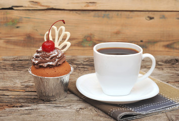 Cupcake with chocolate cream and cherry on old wooden background
