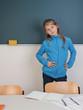 Schülerin steht vor Tafel