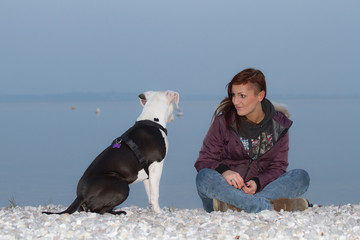 Young woman sitting at the beach with dog