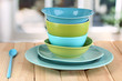Blue and green tableware on wooden table on window background
