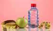 Bottle of water, apple and measuring tape on pink background