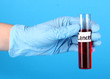 Test tube labeled Cancer in hand on blue background