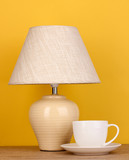 table lamp and cup on yellow background