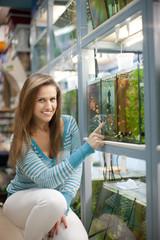 Woman chooses  fish tank