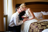 Romantic kiss bride and groom in bedroom