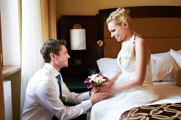 Happy bride and groom in bedroom