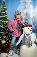 girl with a snowman on the background of a winter landscape
