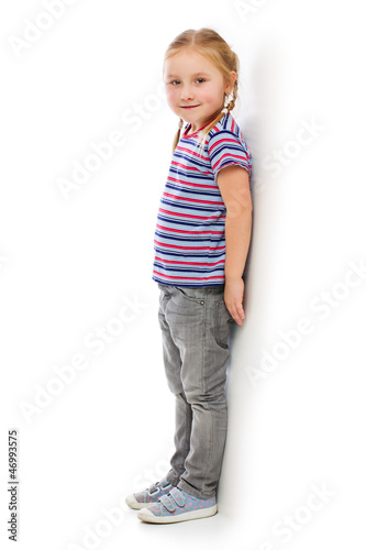 Little girl leaning against a white wall.