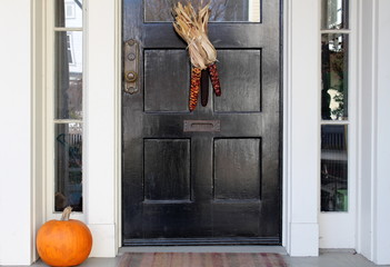 Black door with indian corn and pumpkin on doorstep