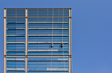 workers washing windows high building