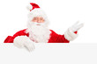 Santa Claus posing behind a billboard and gesturing