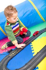 Kleiner Junge spielt mit Autorennbahn