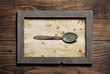 Metal spoon framed on old wood background