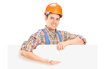 Construction worker posing behind a panel and gesturing