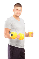 Young man holding a dumbbell and glass of fresh orange juice