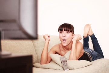 Frau jubelnd vor dem Fernseher