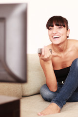 Schöne Frau lacht über einen Film im TV