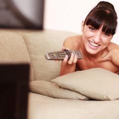 Junge glückliche Frau beim Fernsehen