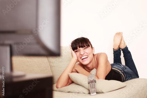 Attraktive Frau lacht über das Fernsehprogramm