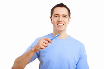 Young man at home brushing teeth