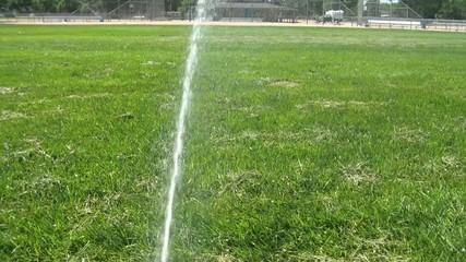 Sprinkler Watering Baseball Field in Sun