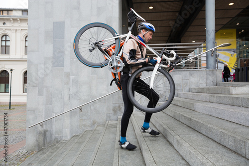 Male Cyclist With Bicycle On His Shoulder Walking Up Steps