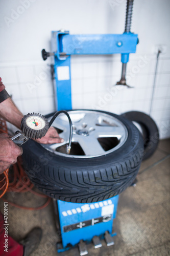 Auto mechanic in a garage checking the air pressure in a tyre