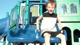 Boy and Puppy Slide Together at Playground