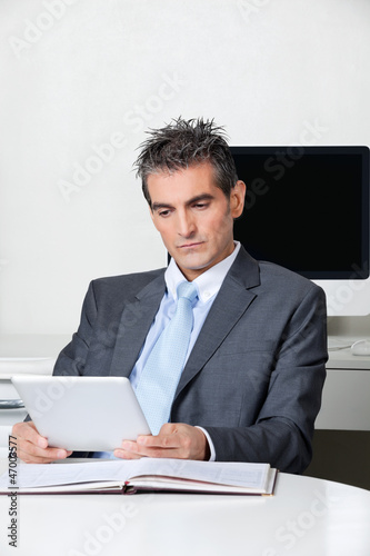 Businessman Using Digital Tablet At Desk