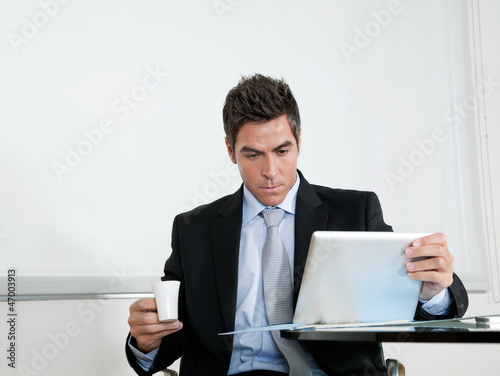 Businessman With Coffee Cup Using Digital Tablet