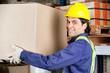 Young Foreman Lifting Cardboard Box