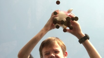 Boy Shaking Coins from Piggy Bank